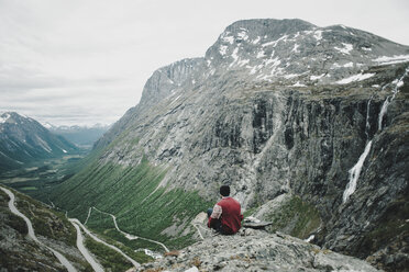 Caucasian man sitting on rock admiring scenic view of valley - BLEF00555