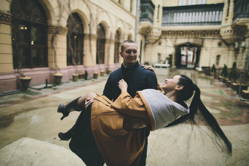Caucasian man lifting and carrying woman in courtyard - BLEF00585