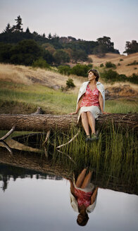 Reflection in lake of Caucasian woman sitting on log - BLEF00642