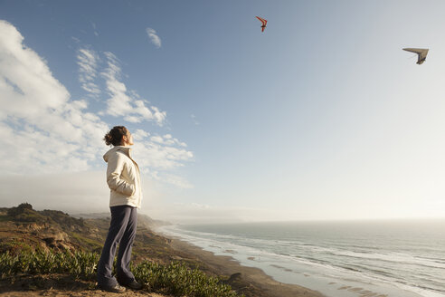 Mixed Race woman standing on beach watching gliders - BLEF00684