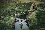 Caucasian woman swimming in pond near rural house - BLEF00693