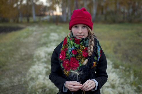 Portrait of Caucasian woman wearing scarf and stocking-cap holding hay seed - BLEF00705