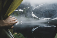 Hand opening tent flap near foggy river - BLEF00723