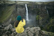 Caucasian woman sitting on cliff photographing waterfall - BLEF00726