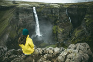 Caucasian woman sitting on cliff admiring waterfalls - BLEF00729
