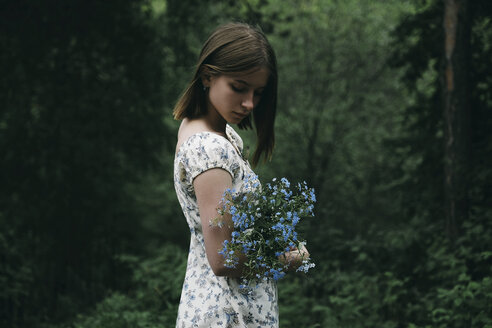 Caucasian woman holding flowers in forest - BLEF00744
