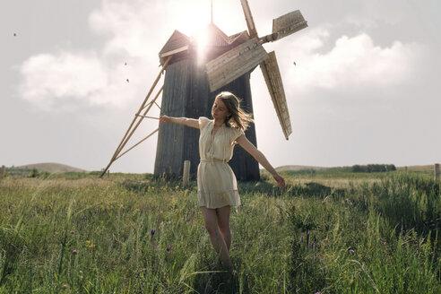 Caucasian woman balancing in grass near windmill - BLEF00756