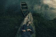 Caucasian woman laying on upside-down boat near lake - BLEF00762
