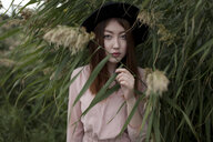Asian woman standing in foliage - BLEF00795