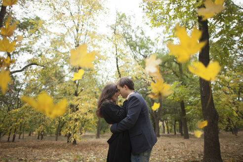 Autumn leaves falling near hugging Caucasian couple - BLEF00798