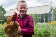 Caucasian boy holding rooster on farm - BLEF00810