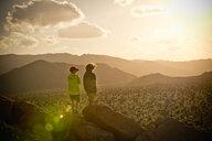 Boys standing on rock admiring desert landscape - BLEF00852