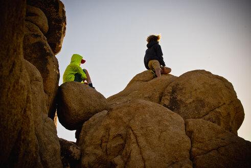 Boys sitting on rocks under blue sky - BLEF00855