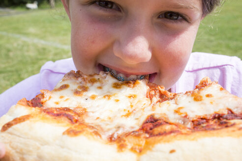 Close up of Caucasian girl with braces biting pizza - BLEF01047