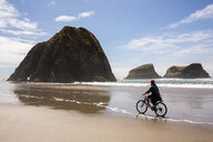 Caucasian woman riding bicycle on beach - BLEF01056