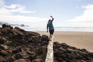 Caucasian woman balancing on log on rocks at beach - BLEF01059