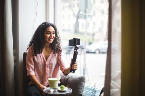 Confident young female influencer vlogging through mobile phone on tripod sitting by window at creative office - MASF11914