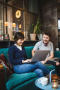 Smiling multi-ethnic male and female entrepreneurs discussing over laptop on sofa at office - MASF11926