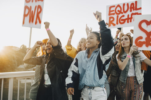 Young women shouting while protesting for equal rights against sky - MASF12031