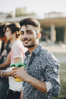 Portrait of smiling young man enjoying drink with friend in concert - MASF12076