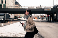 Side view of young woman holding mobile phone while crossing road in city during winter - MASF12127