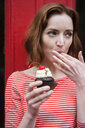 Caucasian woman holding a cupcake licking finger - BLEF01182