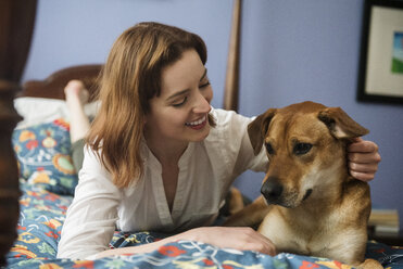 Caucasian woman and dog laying on bed - BLEF01188