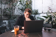 Young man sitting at table using laptop - FBAF00455