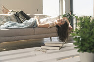 Relaxed young woman lying on couch - UUF17257