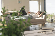 Relaxed young woman lying on couch with a drink - UUF17260