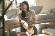 Happy young woman sitting on the floor at home with cell phone - UUF17272