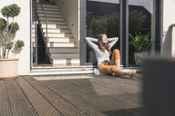 Young woman sitting on terrace at home enjoying the sunshine - UUF17287