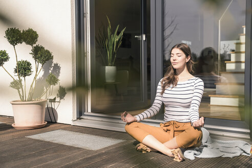 Young woman sitting on terrace at home practicing yoga - UUF17299