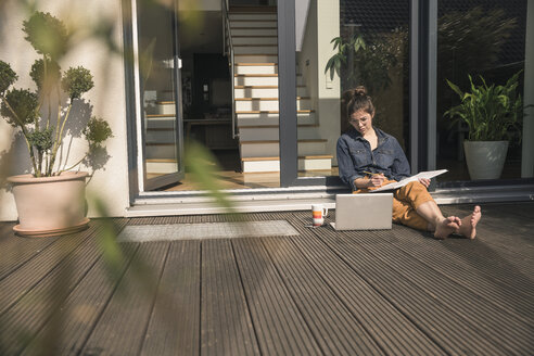 Young woman sitting on terrace at home working with book and laptop - UUF17302