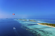 Maledives, South Male Atoll, paraglider flying along an atoll, aerial view - AMF06968
