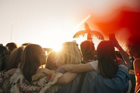 Rear view of friends enjoying music festival against sky in summer - MASF12160