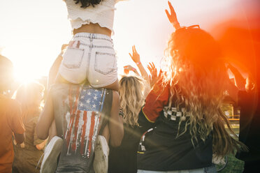 Man carrying friend on shoulder while enjoying in crowd at music event - MASF12169
