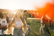 Happy young woman dancing with friends on sunny day in music event - MASF12178