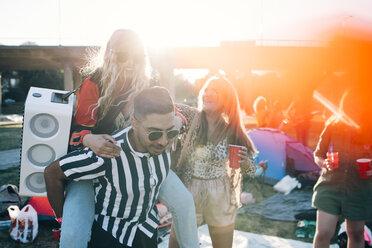 Man piggybacking female friend with speaker while enjoying in music festival - MASF12193
