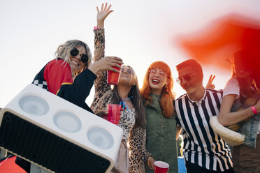 Happy friends with speaker and drinks enjoying in music festival against sky - MASF12196