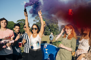 Woman holding distress flare while enjoying with friends during music concert - MASF12205