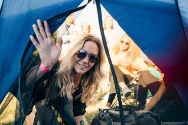 Portrait of smiling woman with friends looking in tent at festival - MASF12217