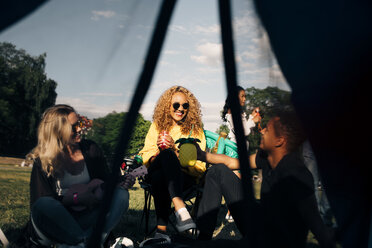 Smiling friends enjoying drinks and music seen through tent at concert - MASF12220
