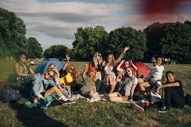 Excited friends sitting on grassy field while enjoying at music festival - MASF12235