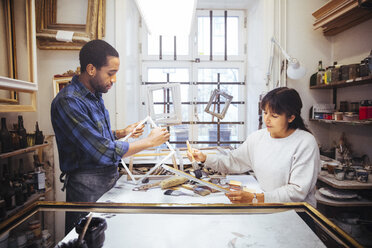Male and female artists making picture frame at workbench in store - MASF12262
