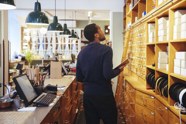 Young male owner looking up at boxes in furniture store - MASF12280