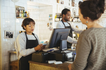 Mature female employee billing customer standing at checkout counter in delicatessen - MASF12286