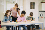 Teacher looking at students writing at desk in elementary classroom - MASF12304