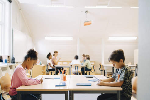 Boy and girl writing at desk while friends learning with student in background - MASF12319