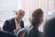 Confident mature businessman discussing with businesswoman during meeting at creative office - MASF12355